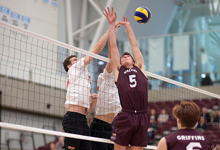 Caleb Weiss battles two Dinos for a ball at the net on Friday (Chris Piggott photo).