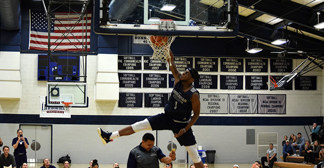 Khalil Rhett '18 throws down the winning dunk over assistant coach Ricky Hernandez in the Hoops Mania dunk contest.