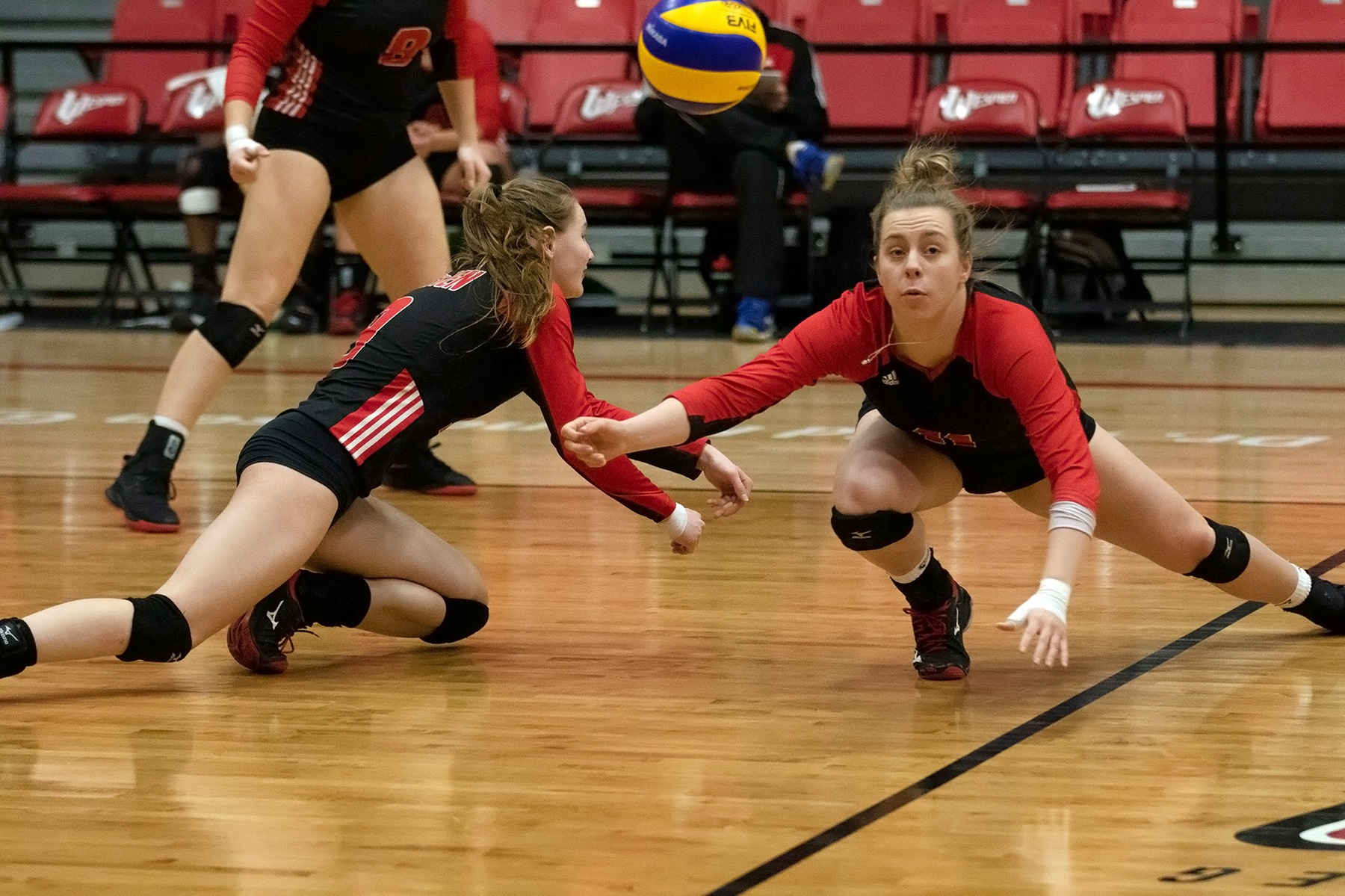 Wesmen Jess Friesen (right) and Emma Parker hit the floor looking to dig up a ball during Winnipeg's loss to the Alberta Pandas on Saturday, February 16, 2019. (David Larkins/Wesmen Athletics)