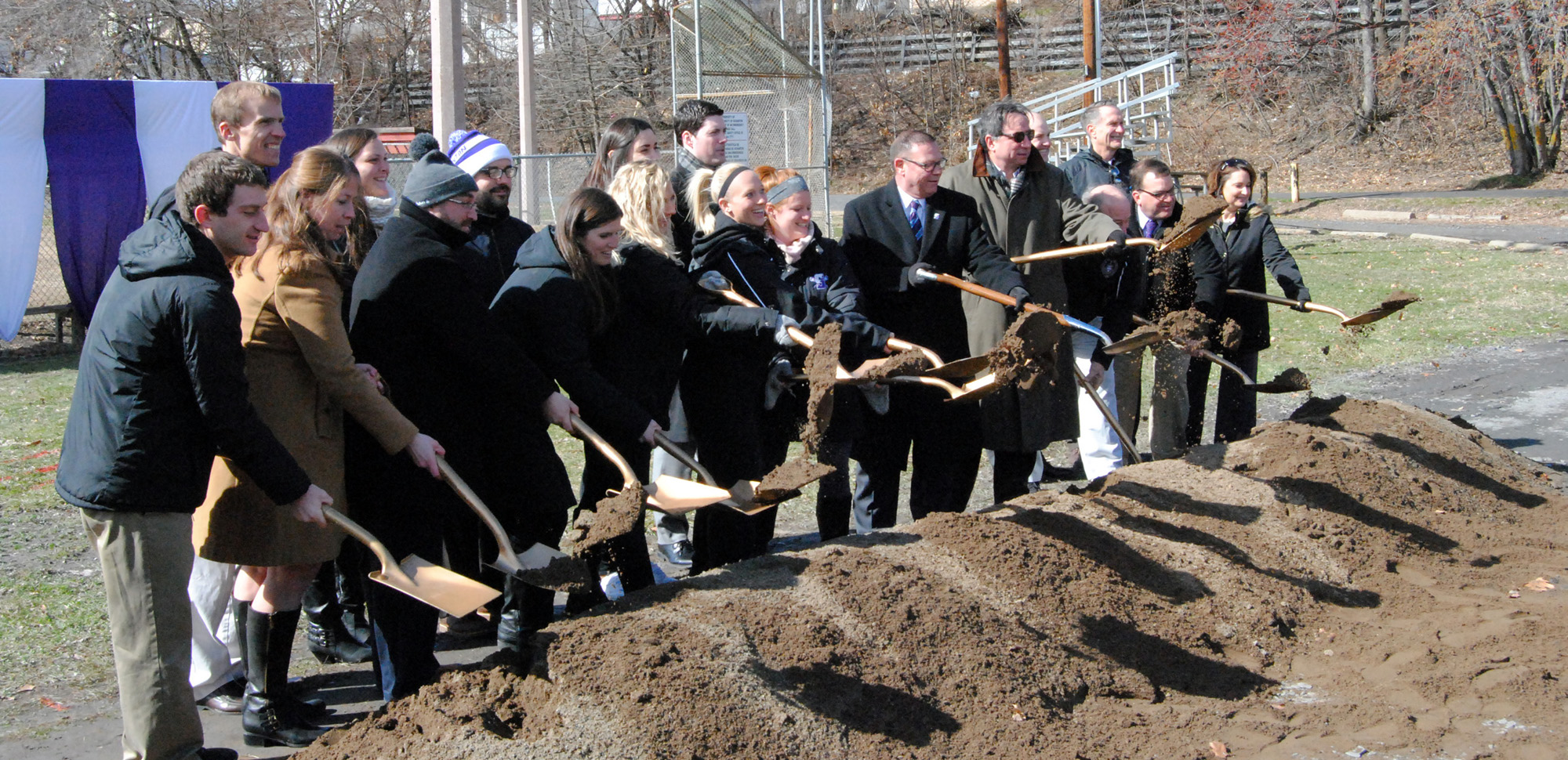 Members of the athletics department take part in the groundbreaking at the South Side Athletics Campus.
