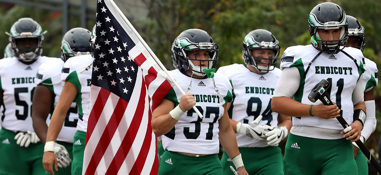 The Endicott football team enters the field with an American Flag.