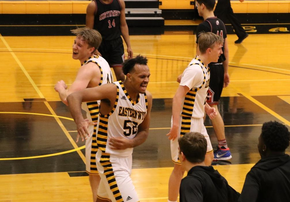 Sophomore Karl Drammeh (center) celebrates with sophomores David Höök (left) and Jonatan Arvidsson (right) near the end of EWC's 90-68 win against Northwest Saturday.