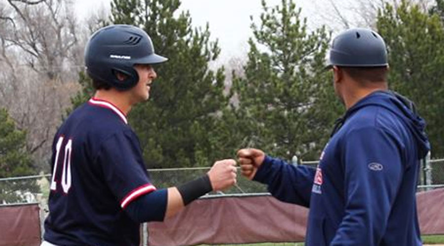 Ryan Moritz and third base coach Jamel Cervantez fist bump after Moritz's first triple of the season in Hutchinson's 6-1 win over Redlands on Tuesday at Hobart-Detter Field. (Bre Rogers/Blue Dragon Sports Information)