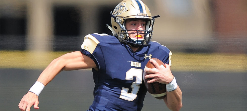 Gallaudet's Jake Bonheyo rushes the football in a home game at Hotchkiss Field. Jake is wearing a navy blue jersey with a white #3 on it. He has a buff helmet on. He carries the football in his left hand.