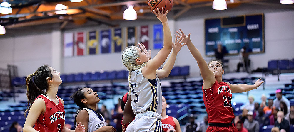 Gallaudet's Emelia Beldon shoots the ball over a defender from Rutgers-Camden/ Beldon shoots the ball with her right hand. Beldon is wearing a gray women's basketball uniform for GU. It is a game inside the Field House. The defender (right) has her right arm outstretched trying to block Beldon's shot. Beldon (center) gets the shot off and over the outstretched arm of the defender.