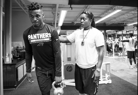 Hassell works with players during post practice lift. Photo courtesy of the Carolina Panthers