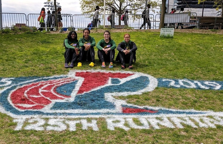 The women's 4x100 team posing next to the 2019 Penn Relays grass-painted signage.
