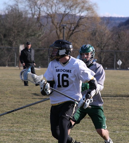 Broome lacrosse player with ball, chased by opponent