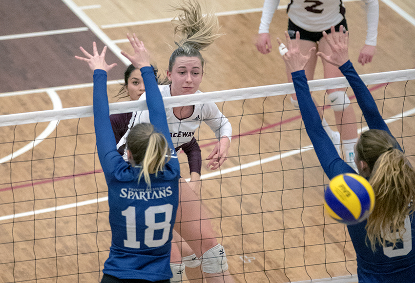 Carly Weber blasts a kill through the Trinity Western block. She tied a MacEwan record with seven aces as the Griffins upset the Spartans 3-2 on Friday night (Eduardo Perez photo).