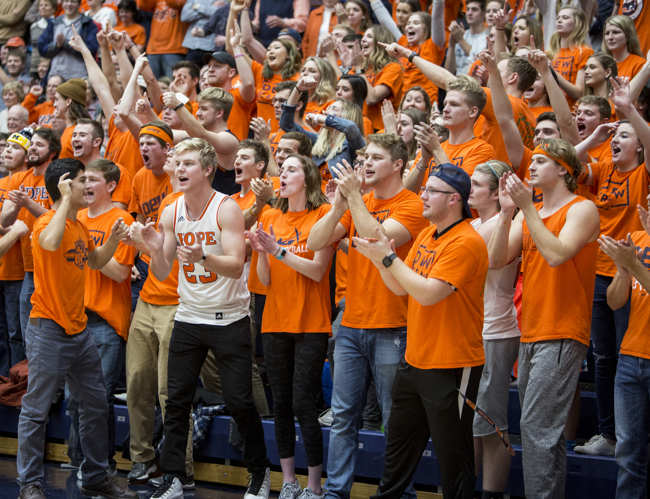 Orange-clad Hope College students lead cheers during a basketball game at DeVos Fieldhouse.