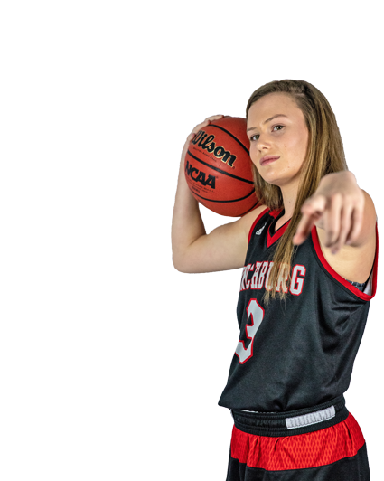 Maggie Quarles holding a basketball and pointing.