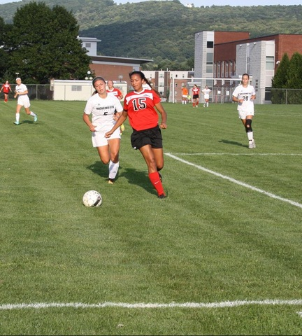 SUNY Broome women's soccer players chasing opponent and ball