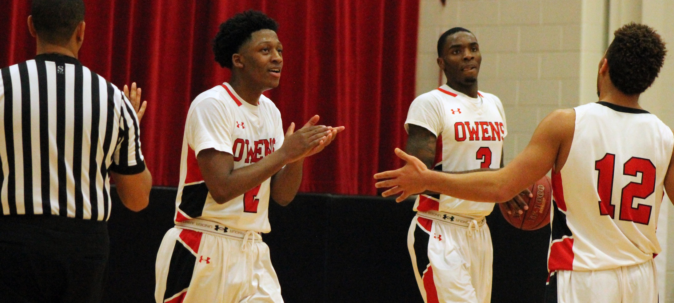 Roy Hatchett (far left) celebrates after a basket with Shondell Jackson (3) and Mason Durden (12). Photo by Nicholas Huenefeld/Owens Sports Information