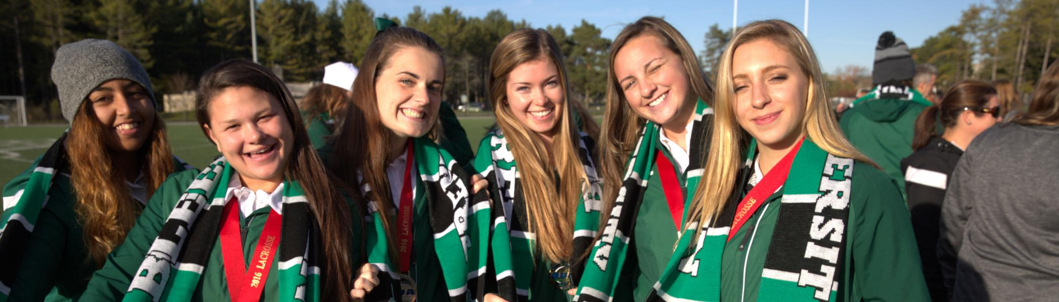 Women's Lacrosse team members smile with their OUA Bronze Medals