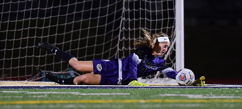 Gallaudet women's soccer goalie Payton DeGraw makes a diving save in a night game.