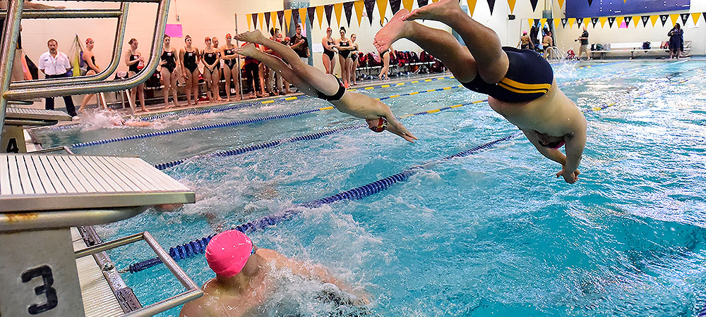 A Gallaudet men's swimmer dives, head first, into the deep end of the pool during the 200-yard freestyle relay. Another Bison swimmer just touched the wall and is looking back at their teammate diving into the water. Go Bison!