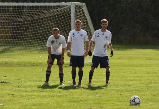 TJ Couch, Peter Williams, and Patrick Vaughn defending the goal during a penalty kick