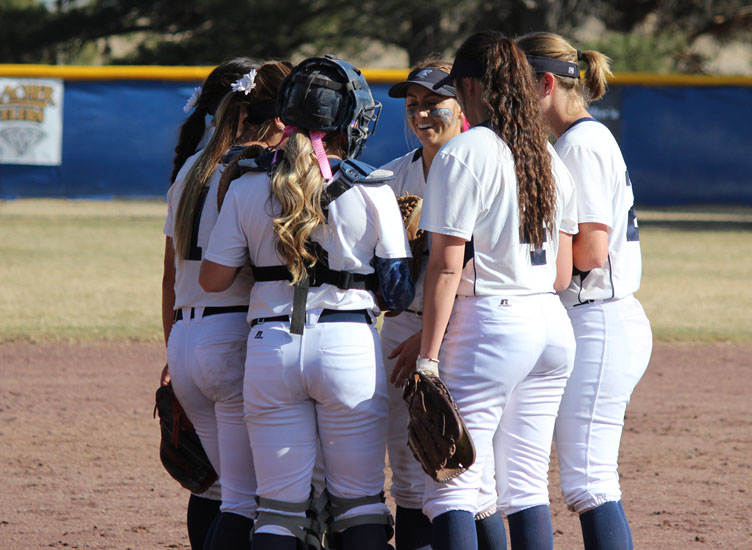 The CCC Lady Trojans softball team meets on the infield during a game earlier this season.