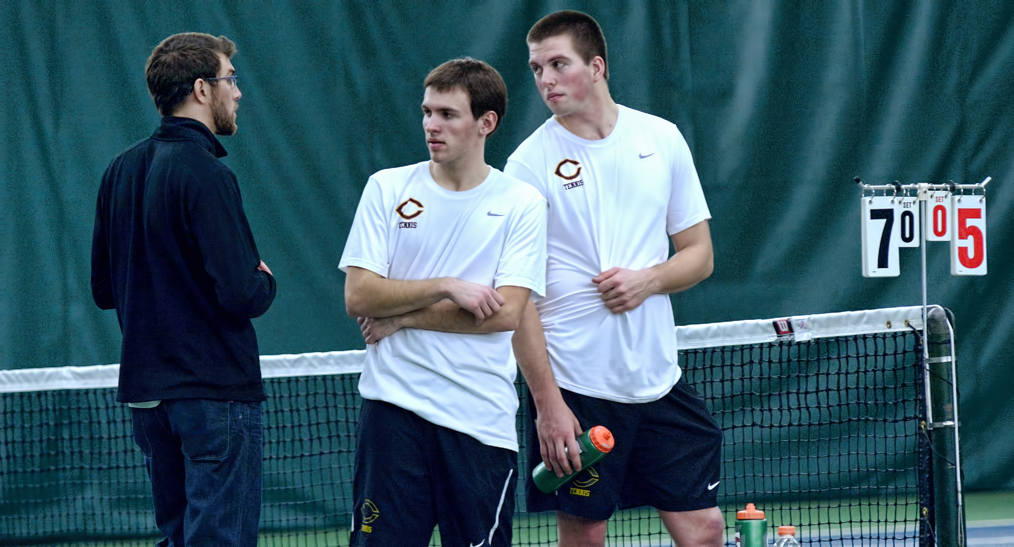 The Cobber No.1 doubles team of David Youngs (L) and Isaac Toivonen talk with head coach Joseph Murrey. The tandem won their bout at No.1 doubles and both players claimed singles wins in CC's 5-4 win at St. Mary's.