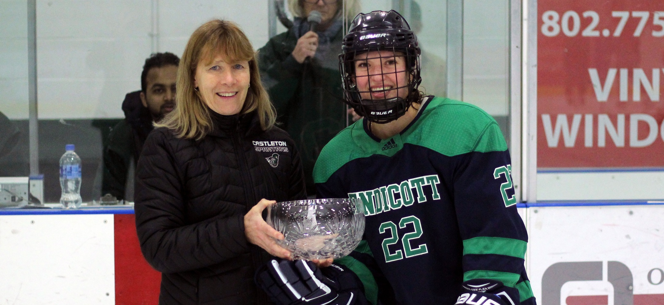 Courtney Walpole accepts the WSYB/Catamount Radio Invitational championship trophy on behalf of the Endicott women's ice hockey team.