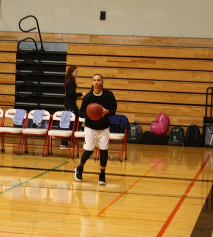 Women's basketball player taking a jump shot during warmups