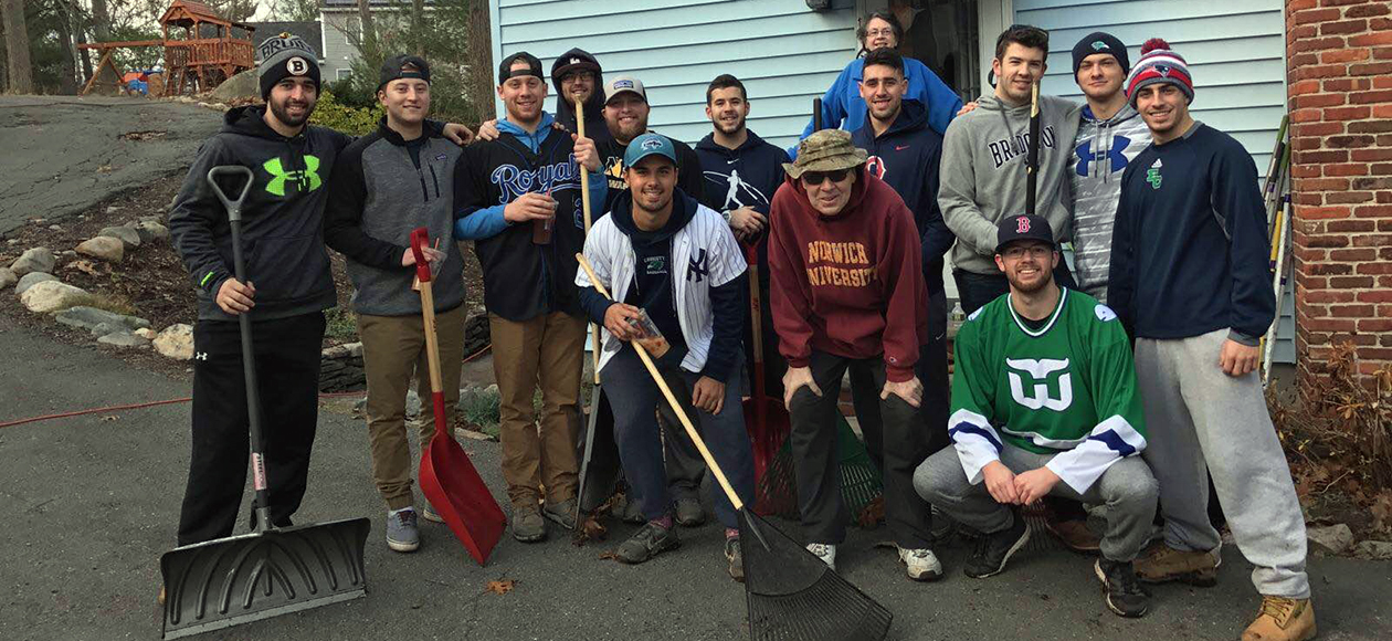 Here is a photo of 14 members of the Endicott baseball team, dressed warmly for the cold weather, holding rakes and snow shovels as they pose for a photo after a day of helping out in the Beverly community by shoveling snow, raking leaves, and assisting with other beautification projects.