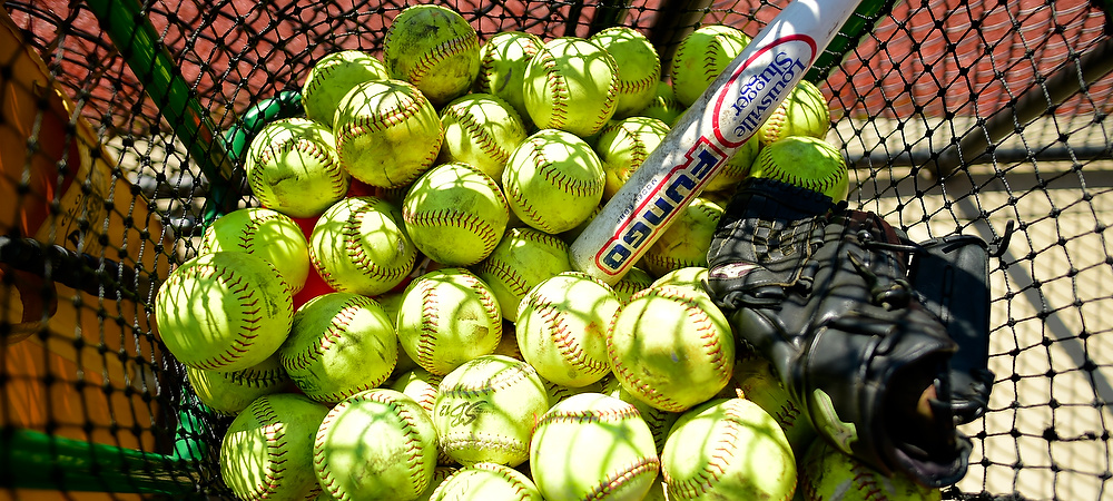 A downward picture of many softballs, black glove, and a white bat all thrown in a basket net.