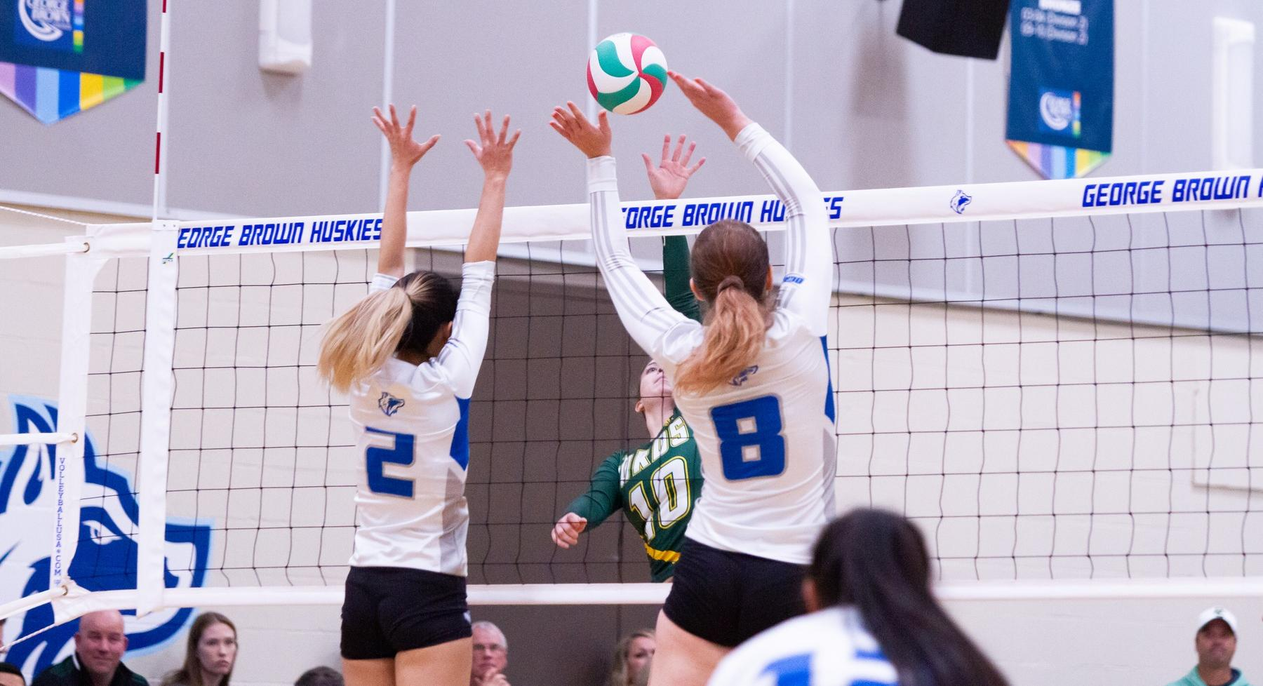 Two Huskies players block at the net