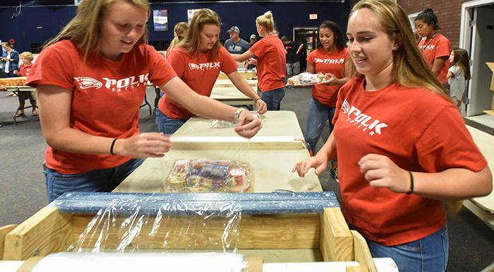 Eagles soccer players prepare meal packs for kids. (Photo by Tom Hagerty, Polk State).
