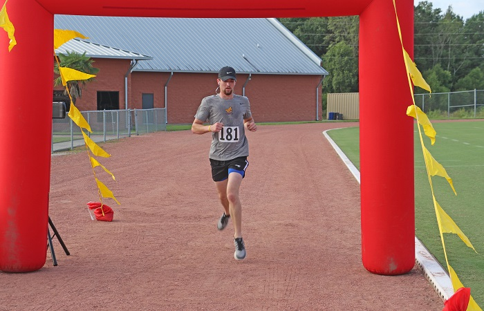 JCJC cheerleader Dakota Finerman crosses the finish line as the overall winner of Saturday's 11th annual Bobcat Hall of Fame 5K Run.