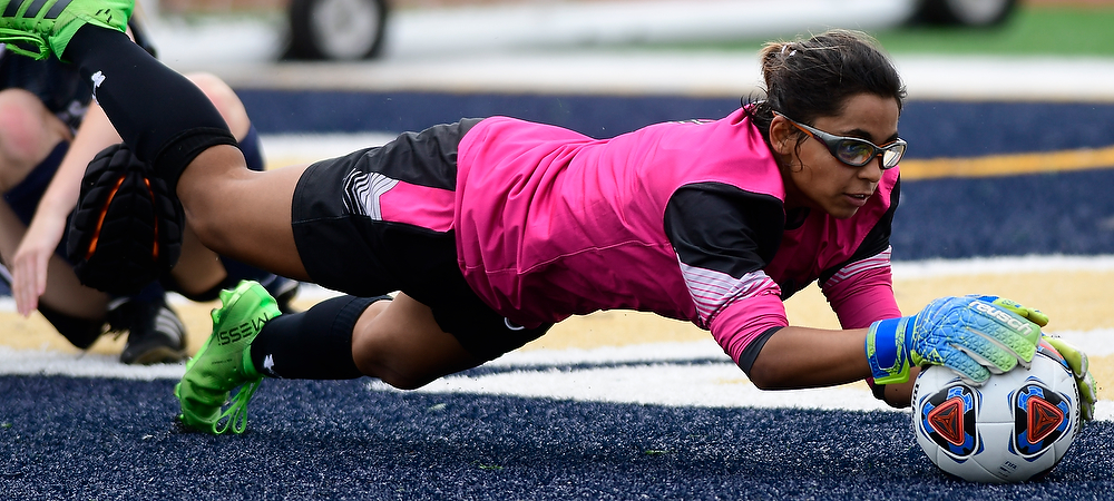 Gallaudet women's soccer goalie Silvya Levesque makes a diving save as she falls to the field turf and grabs a soccer ball with both hands.