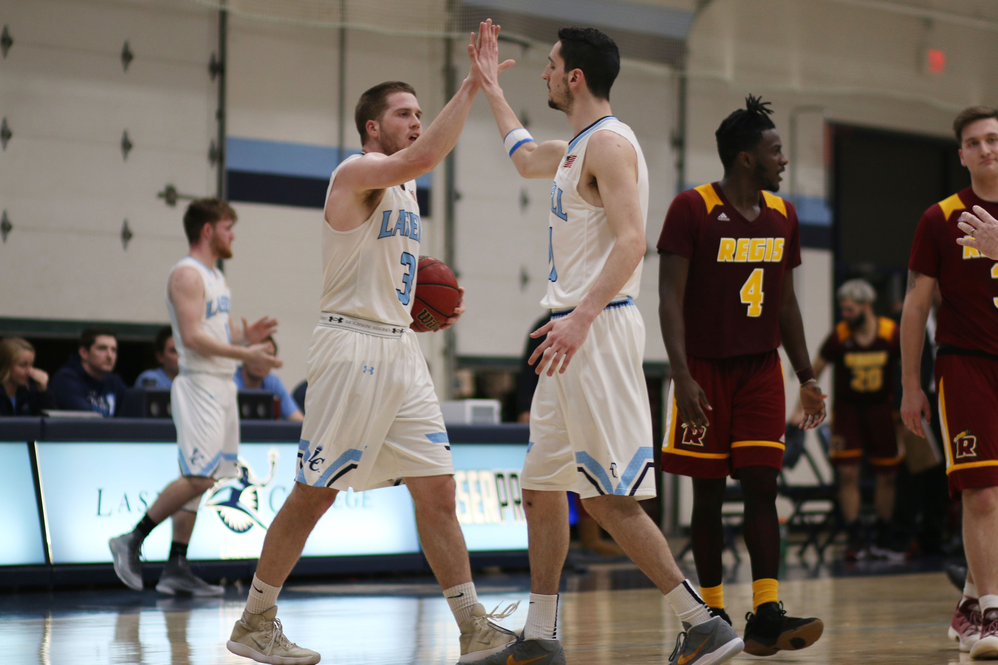 Lasell Men's Basketball rolls past Regis in GNAC playoffs