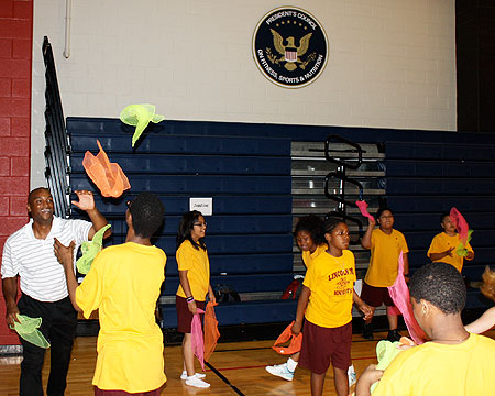 Coach Pride performs juggling activity with kids