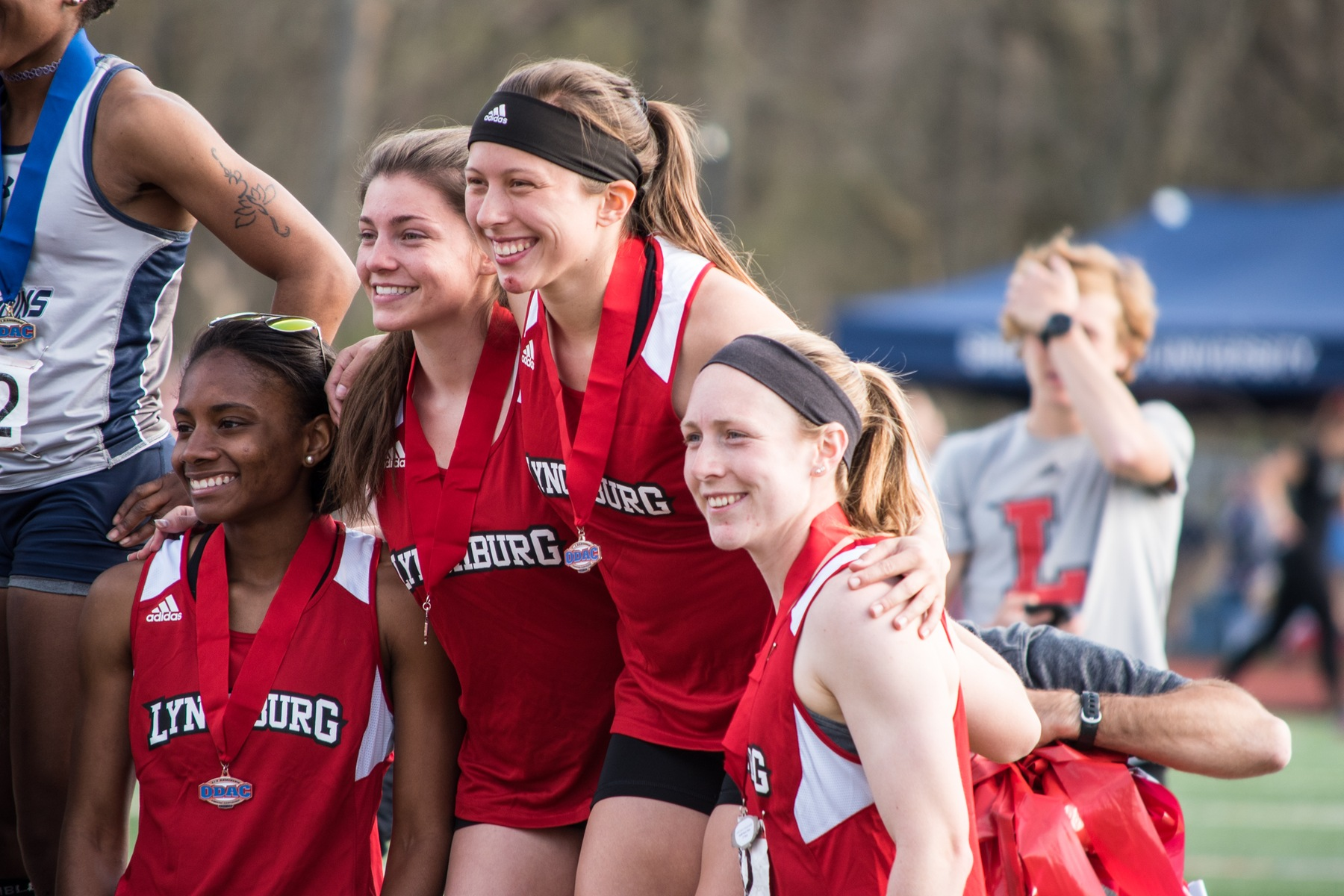 Lynchburg track athletes pose on the podium after winning a relay.