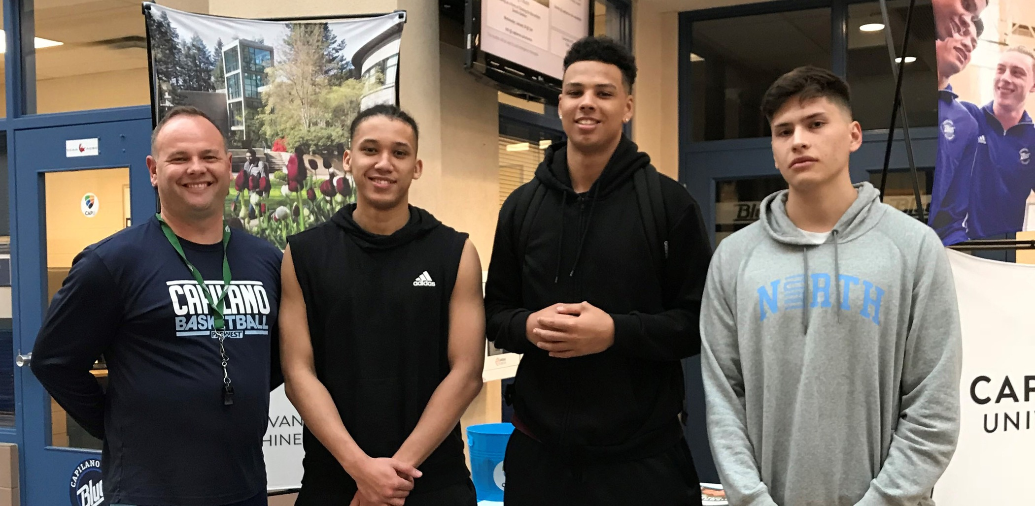 Blues head coach Cassidy Kannemeyer alongside new recruits Jonavan Grant, Rhys Blake, and Sterling Peterson at the CapU men's basketball ID Camp in April.