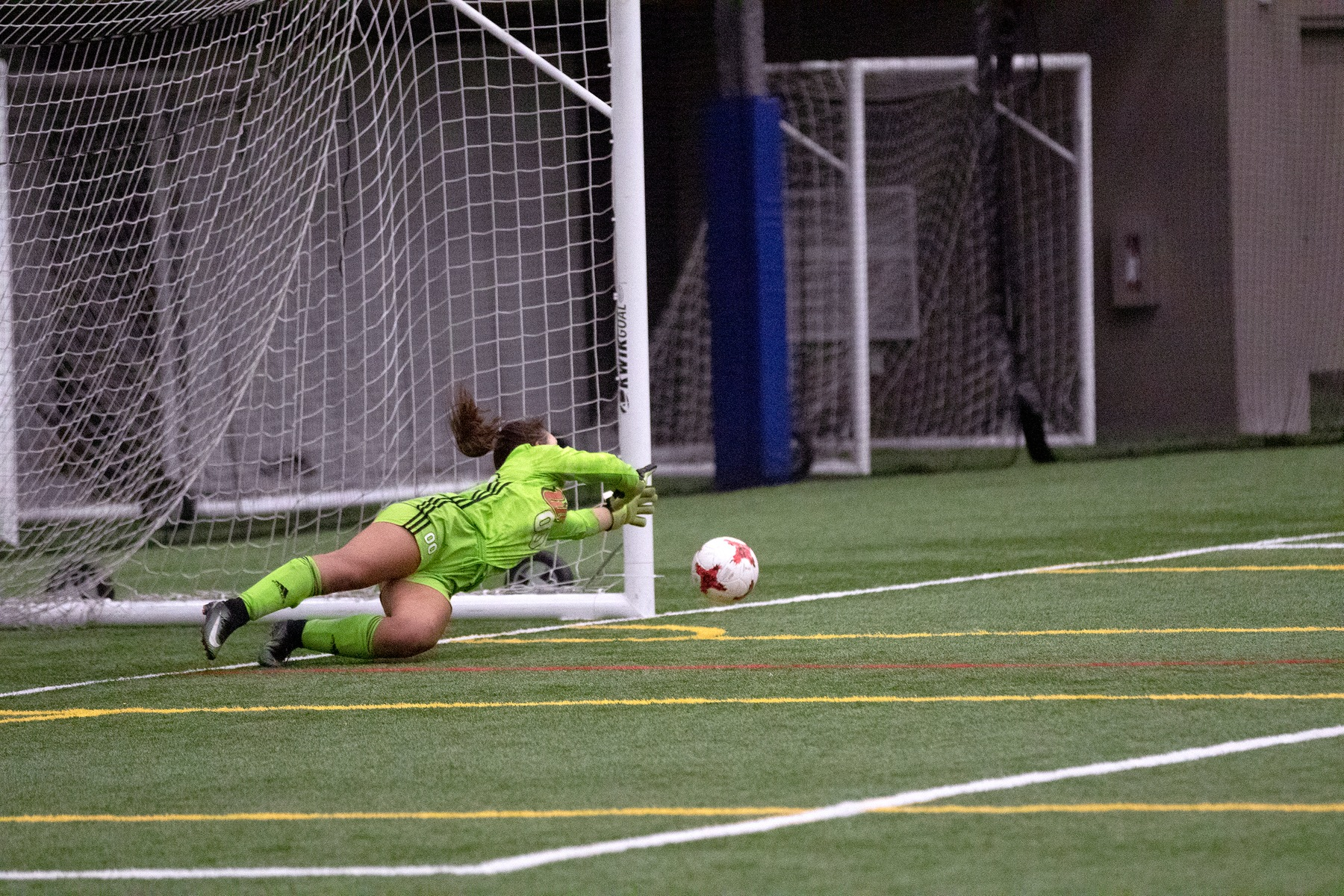 Taryn Raabe dives to make a stop on a Thompson Rivers penalty kick during Canada West conference women's soccer action at the WSF North indoor pitch Saturday, Sept. 21, 2019. (David Larkins/Wesmen Athletics)