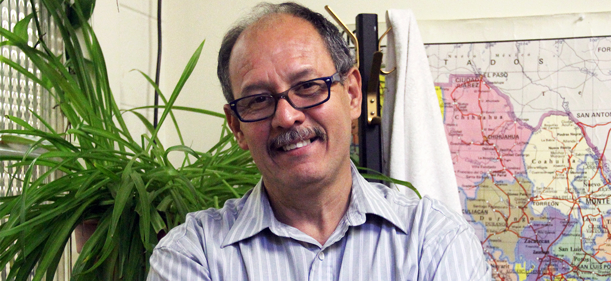 Dr. Sergio Inestrosa, with his dark-rimmed glasses and gray mustache, smiles for a photo in his office. He is wearing a blue collared shirt and is standing in front of a map of the world with a bright, green plant perched on a bookshelf behind him.