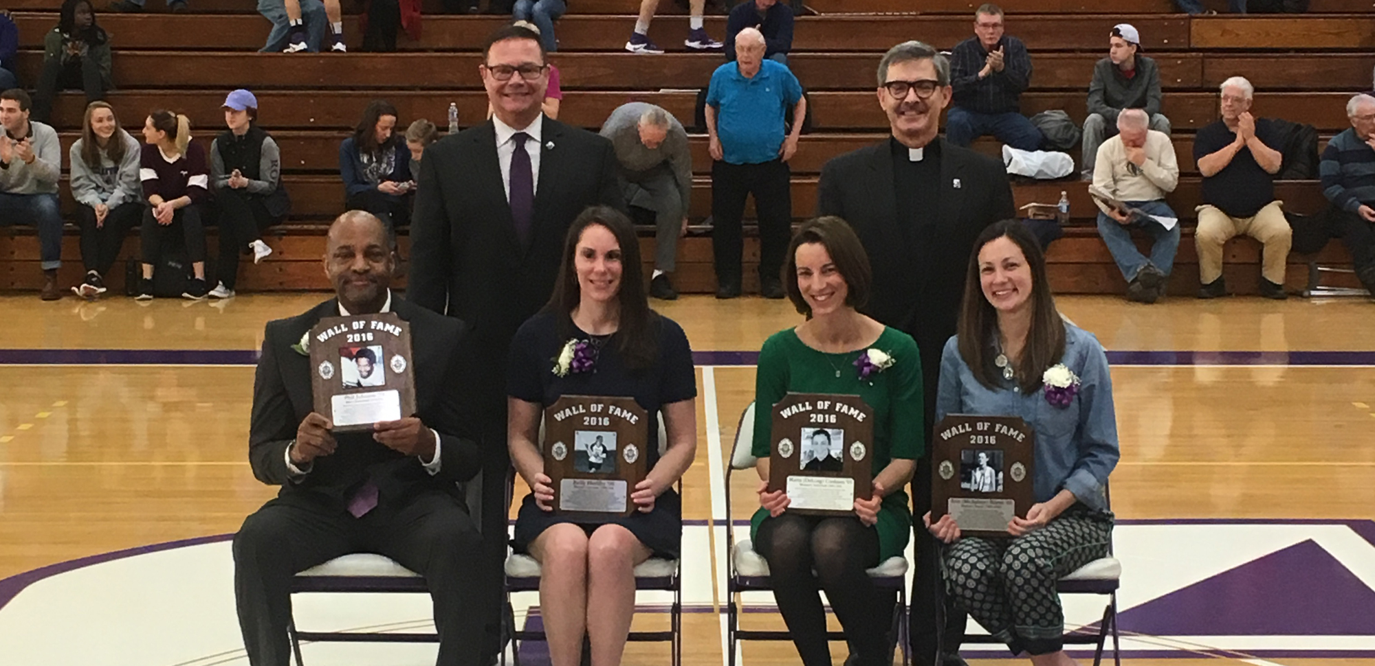 The University inducted the Wall of Fame Class of 2016 during a ceremony in the Long Center on Saturday. The inductees are, seated from left, Phil Johnson '78, Kelly Herlihy '06, Marta (DeLong) Cookson '05, and Erin (Michalisin) Beirne '03. Standing are athletics director Dave Martin and Rev. Kevin P. Quinn, president of the University.