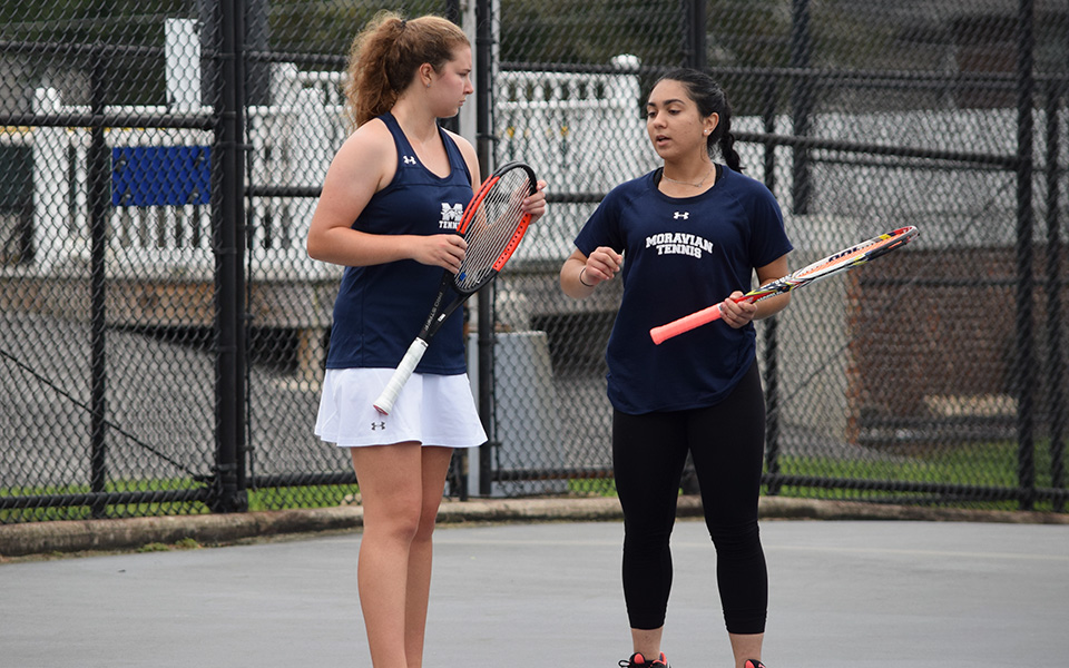 Sophomore Emma Angle and junior Eiman Nazif talk strategy in a doubles match versus Muhlenberg College on Hoffman Courts during the fall 2018 season.