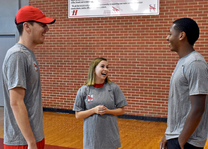 Cross country coach Dan August (left) and runners Ari Oldaker (center) and Milan Branch (right) talk during Wednesday's check-in. Cross country, men's and women's soccer and volleyball each reported for preseason practice.