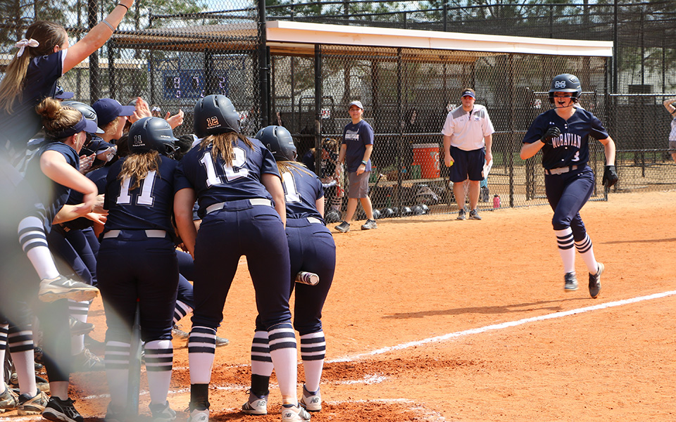 The Greyhounds greet junior Lauren Goetz at home plate after her first inning grand slam versus Thiel College at the Spring Games in Clermont, Florida.