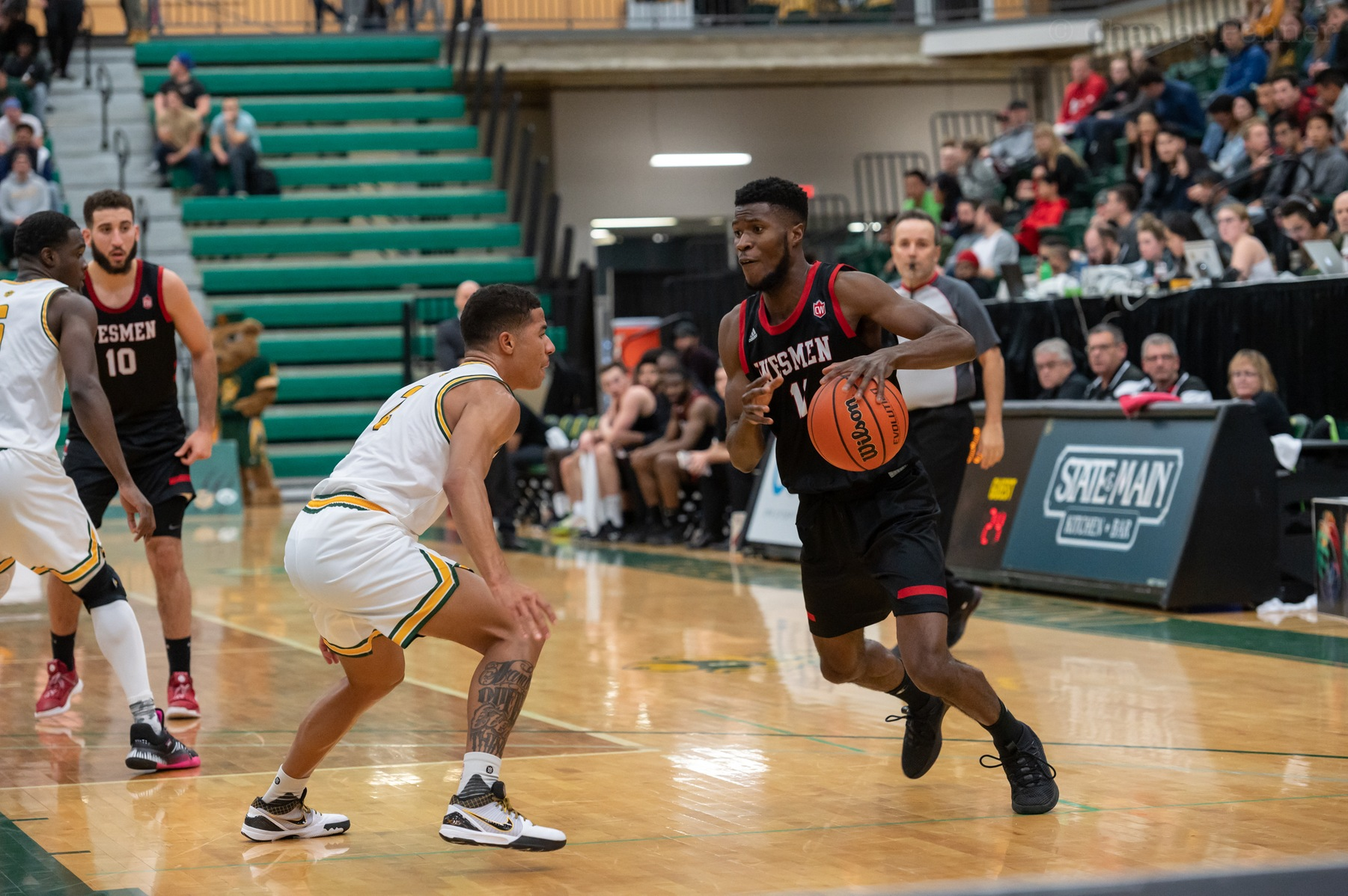 Will Sesay looks to attack the basket during Wesmen men's basketball action at Alberta, Friday, Nov. 8, 2019. (Photo: CombatCaptured/Alberta Athletics)