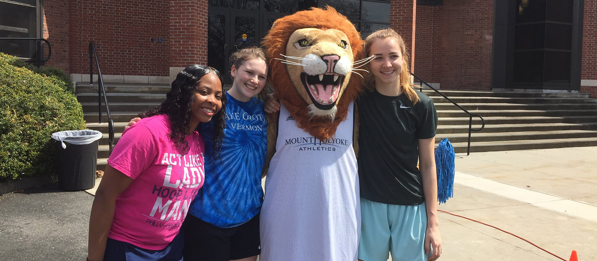 Photo featuring Lyons basketball players, Zahkeyah Allen, Katlyn Grover, PAWS (the Lyons' official mascot) and Annika Brooks.
