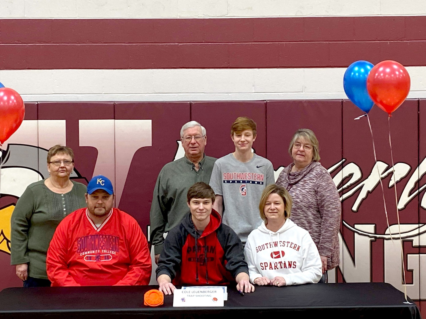 Cole Leuenberger signs with Southwestern's sports shooting team.