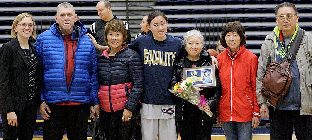 Gallaudet's Lawjen Ashmore (center) is surrounded by her family on Senior Day. Bison women's basketball head coach Stephanie Stevens is on the far left.