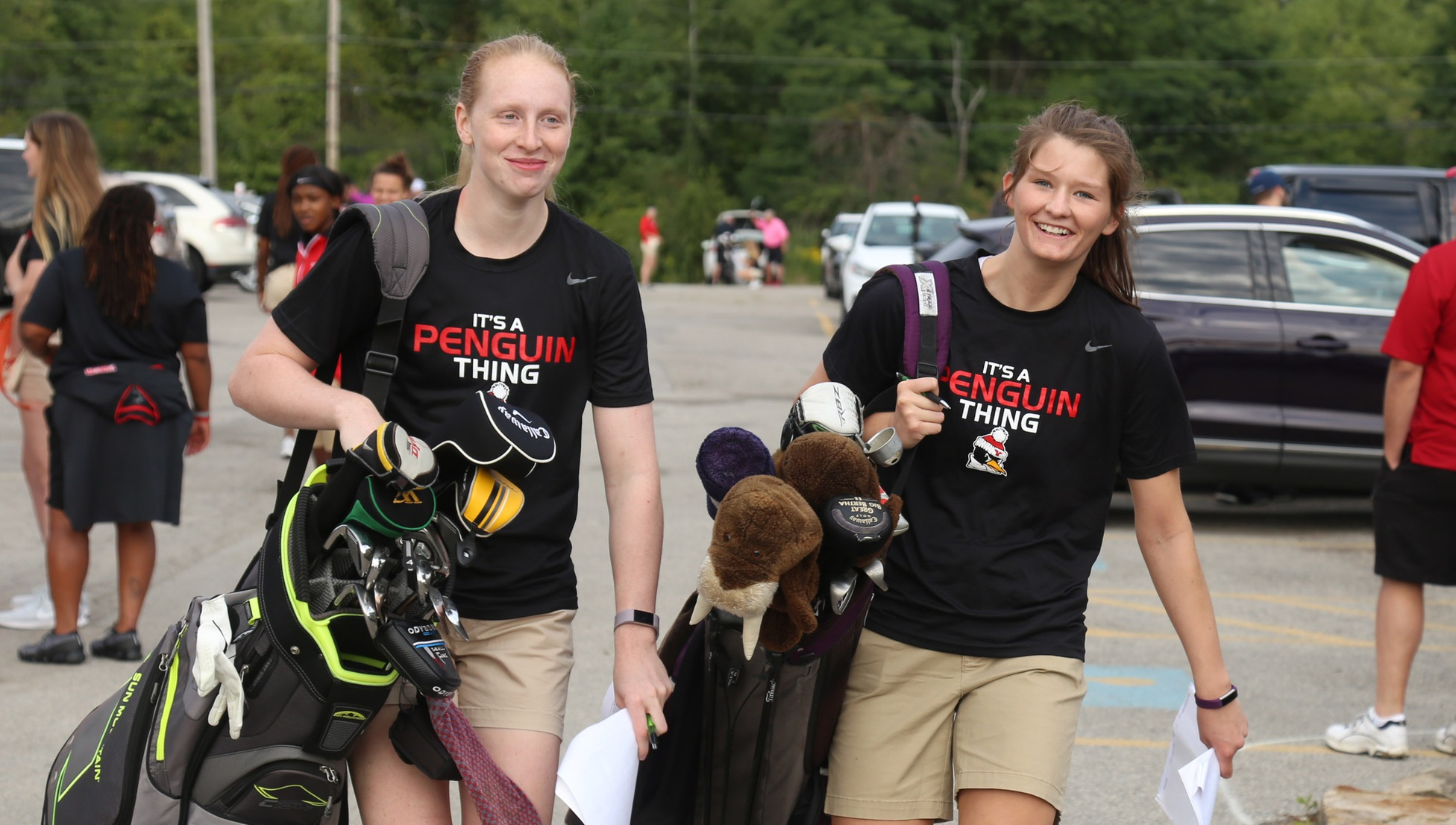 Sarah Cash and Madison Mallory carry golfers' bags prior to the YSU Women's Basketball program's annual golf outing on Aug. 25.