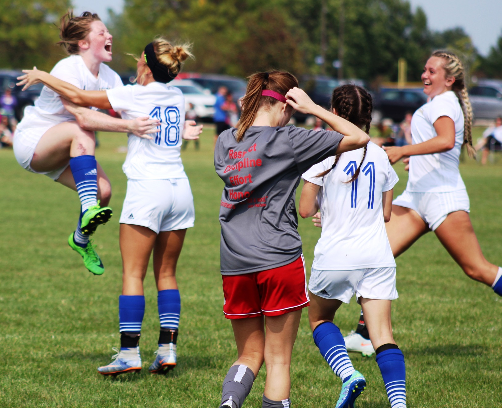 Emma Eden (in air) celebrates after scoring a goal off a header on a corner kick in first half of Sunday's match.