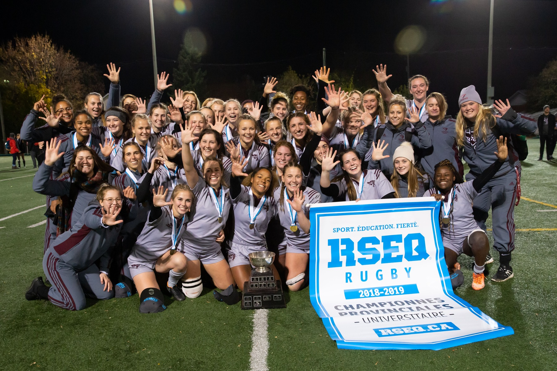 Team holds 2018 RSEQ championship banner at Matt Anthony Field.