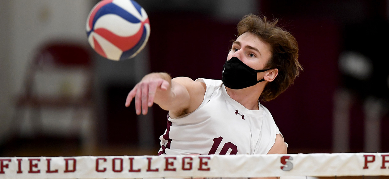 Men's Volleyball Player spiking the ball over the net.