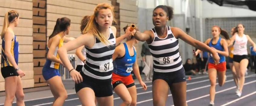 Michelle Fry '15 receives the hand-off from Anifreed Sinjour '12 in today's winning 4x400-meter relay (photo by Sportspix)